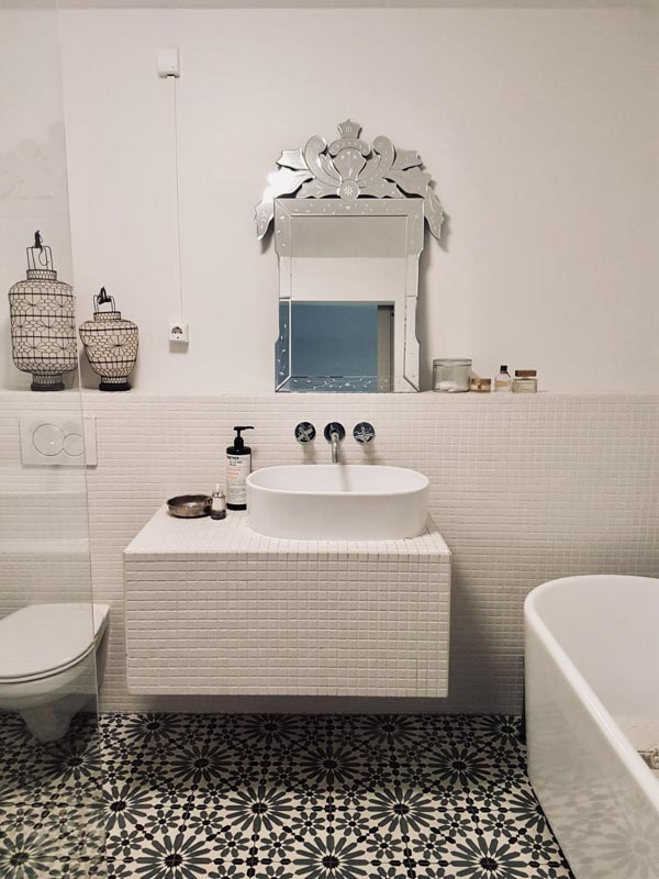 Bathroom before makeover with white walls, white tiles and floor tiles with a motif