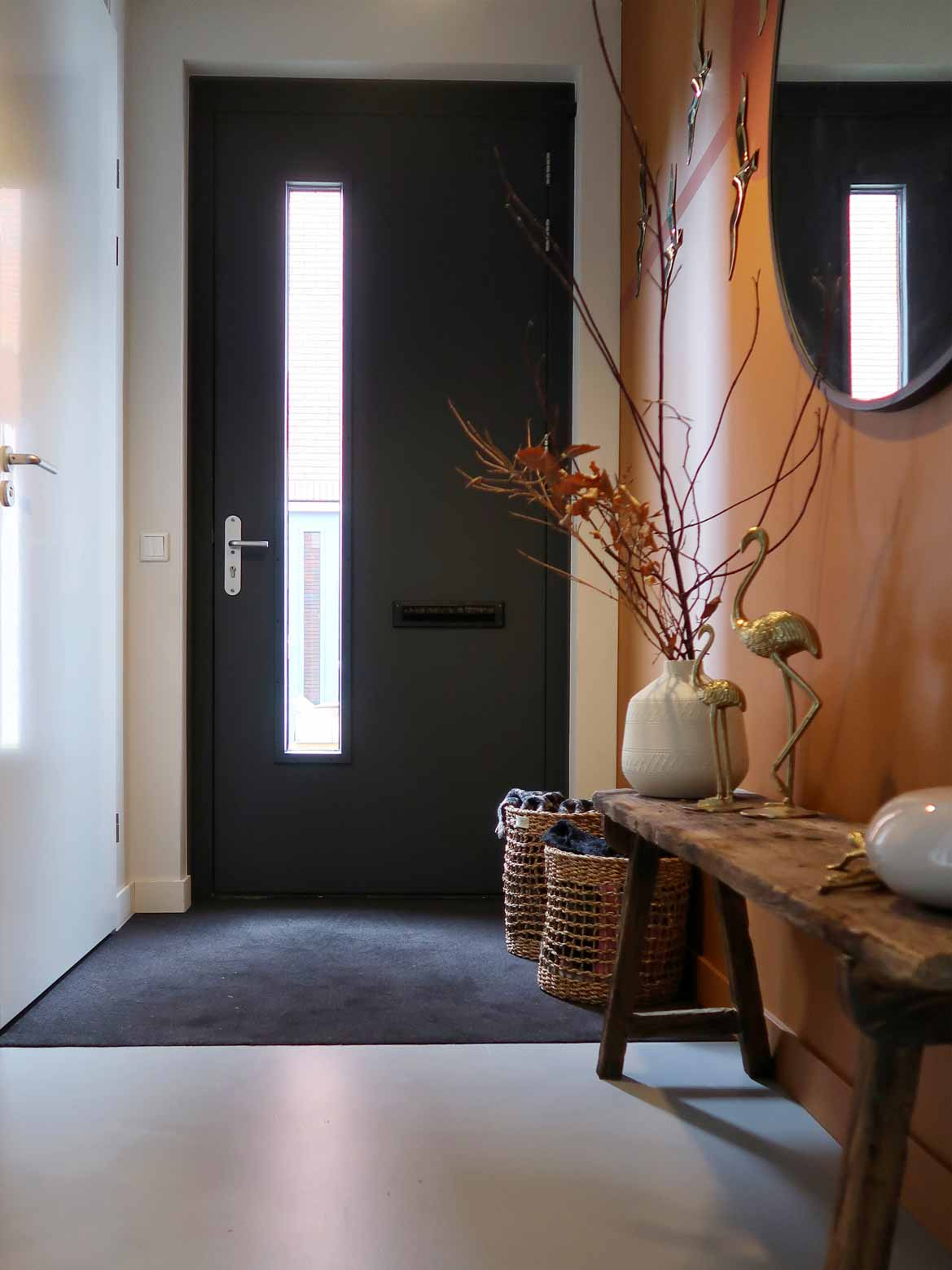 Hallway with large round mirror, caramel and dry terra horizon effect wall, black door, wooden bench