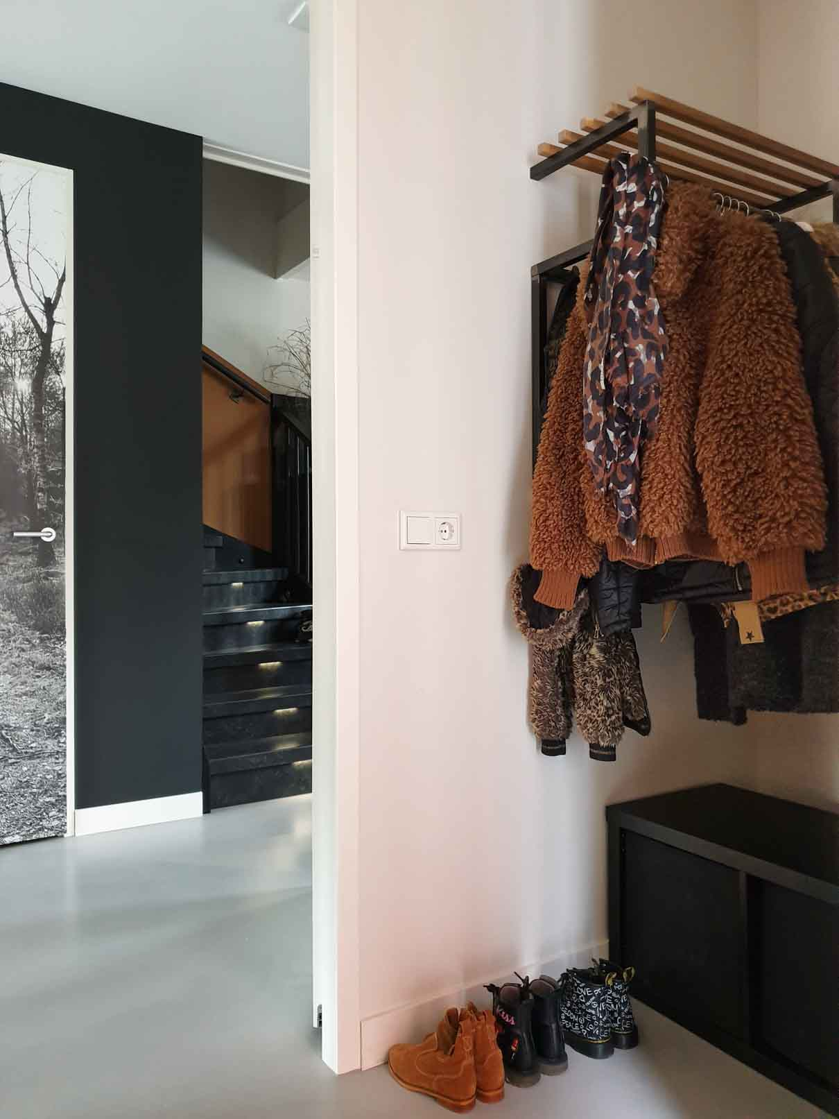 Hallway with white walls, black accents, and wooden and black metal coatrack