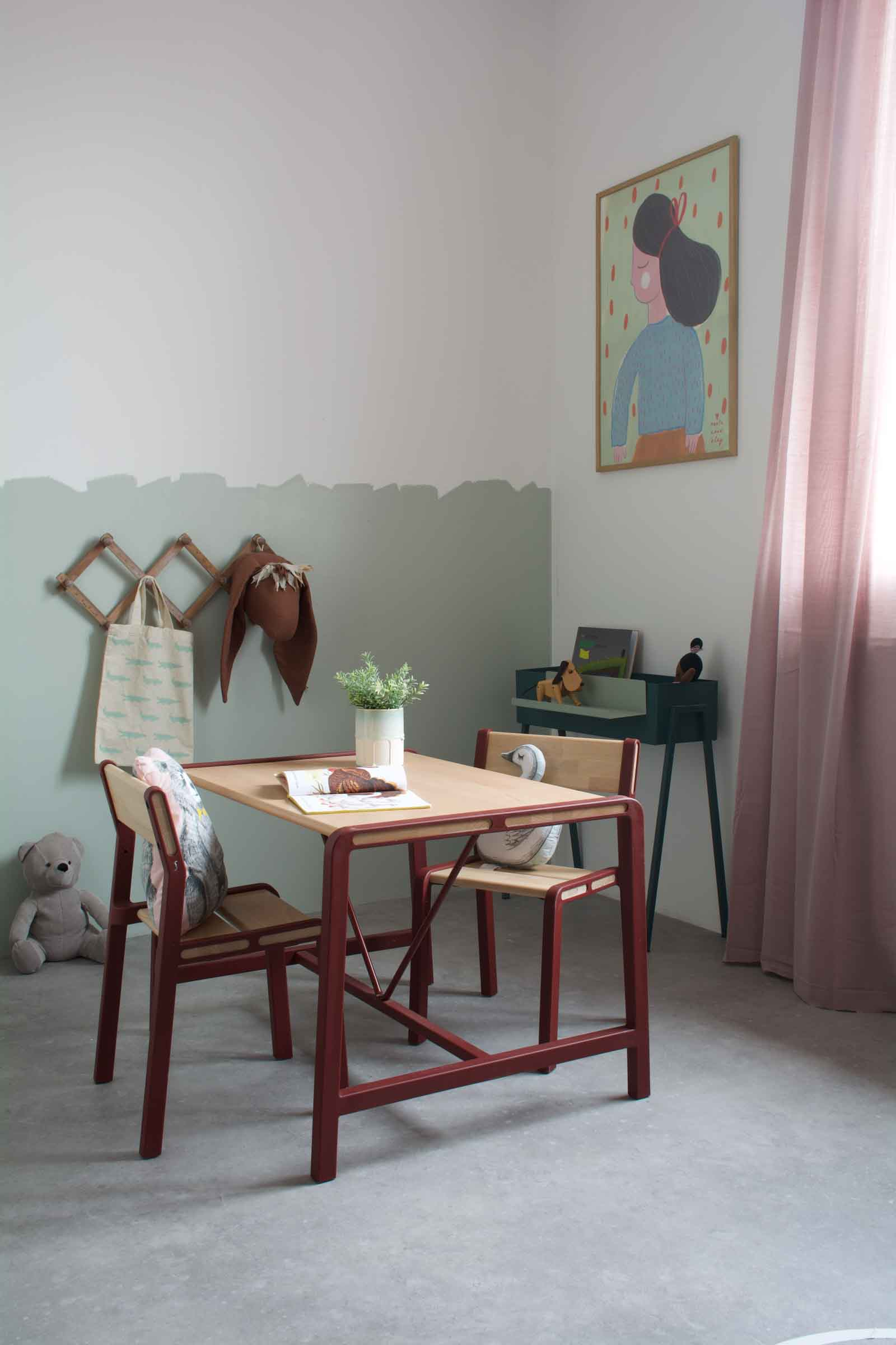 After picture kids room with mint green paneling, a red and wooden table, pink curtains and stuffed