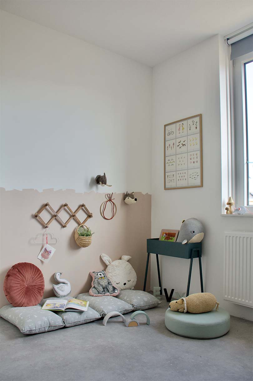 Before picture of kids room with white walls, playfully messy pink paneling and kids stuffed animals