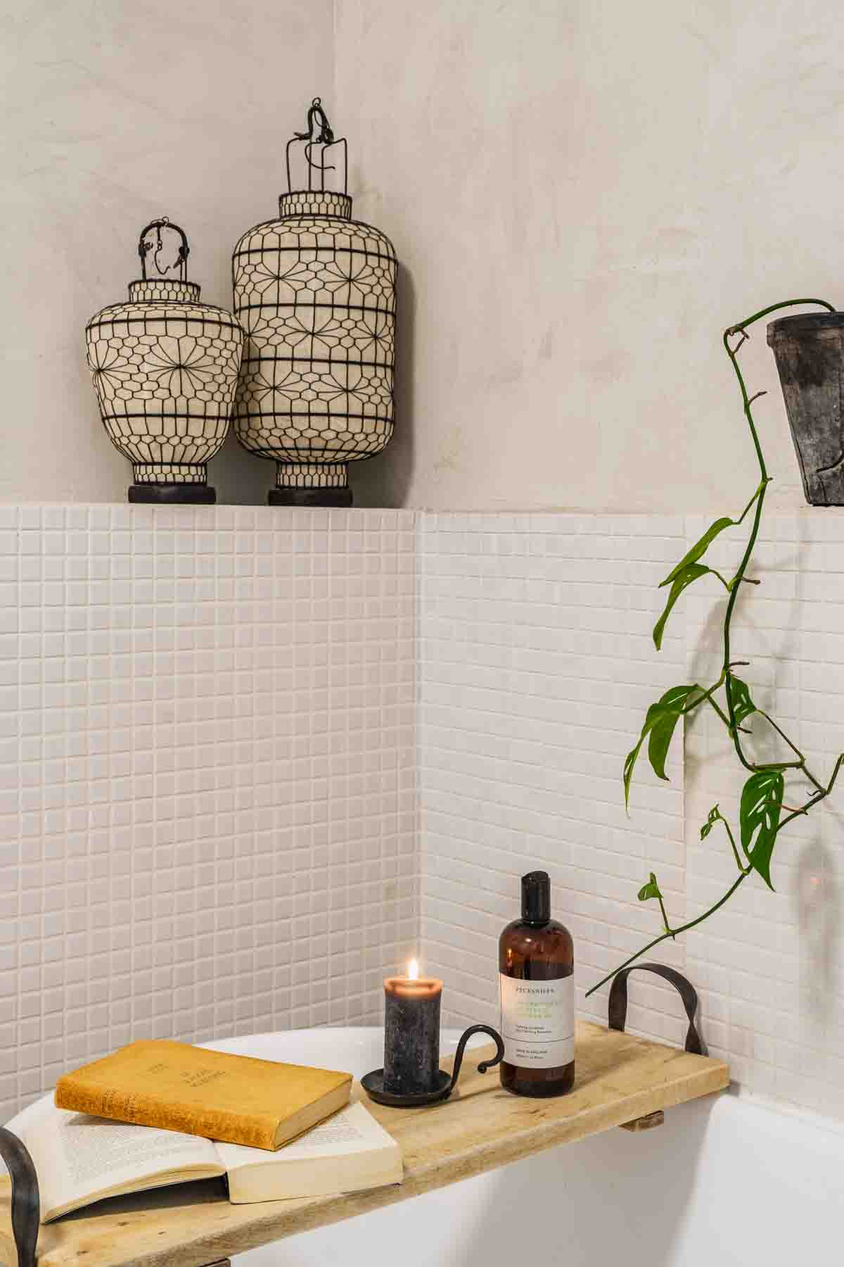 White bathtub with wooden bath table, white tiled and Marrakech Walls painted walls and oriental dec