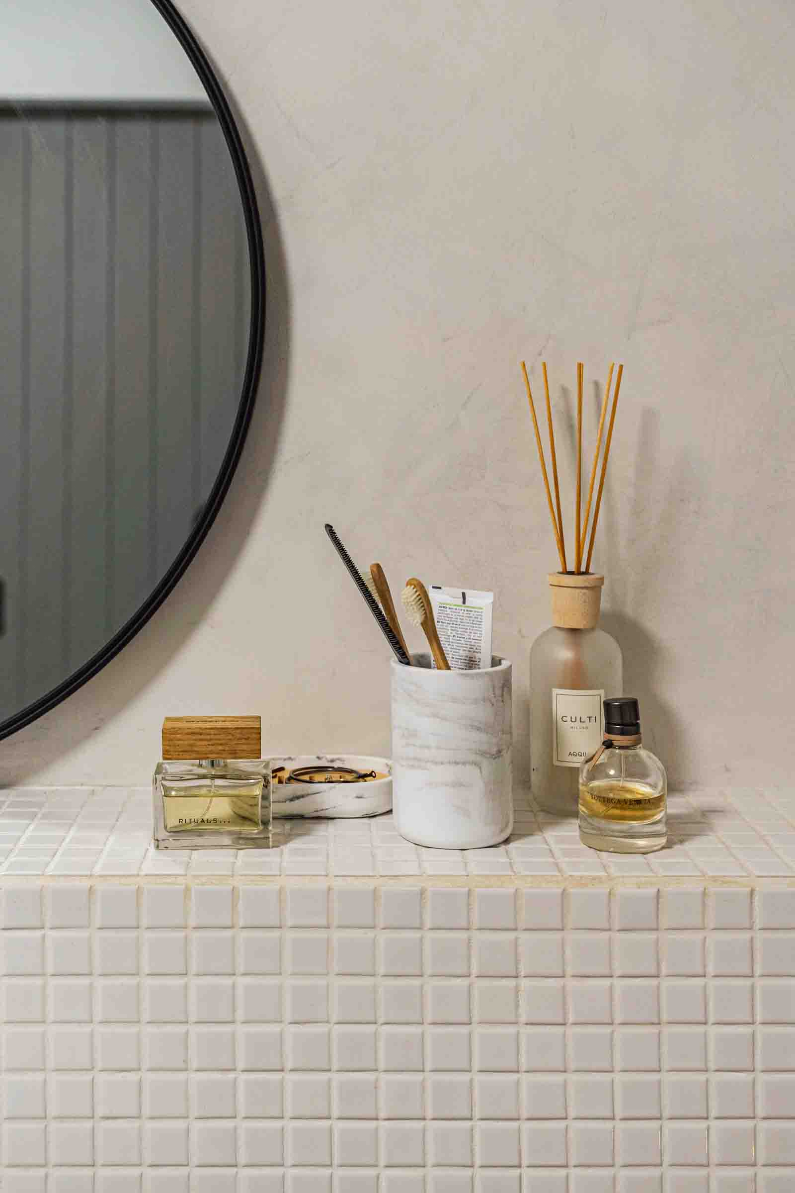 White tiled ledge in bathroom with toiletries