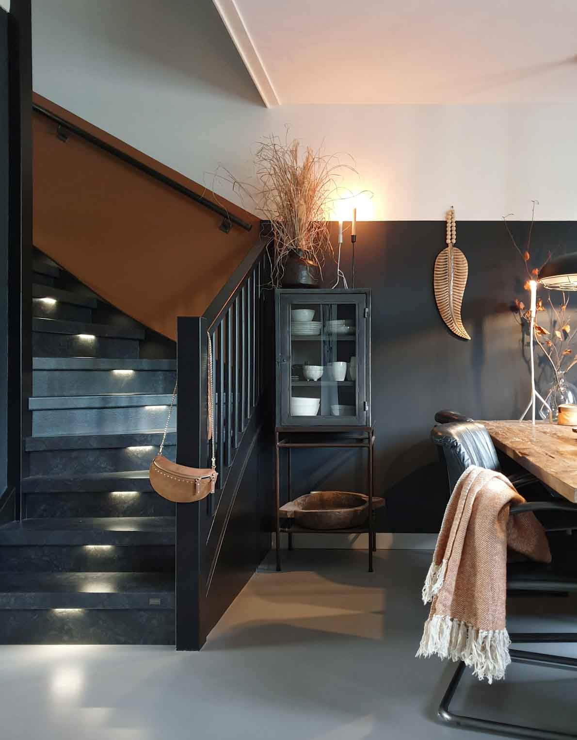 Stairs and dining area with dark grey, caramel, and white walls with panelling and natural and woode