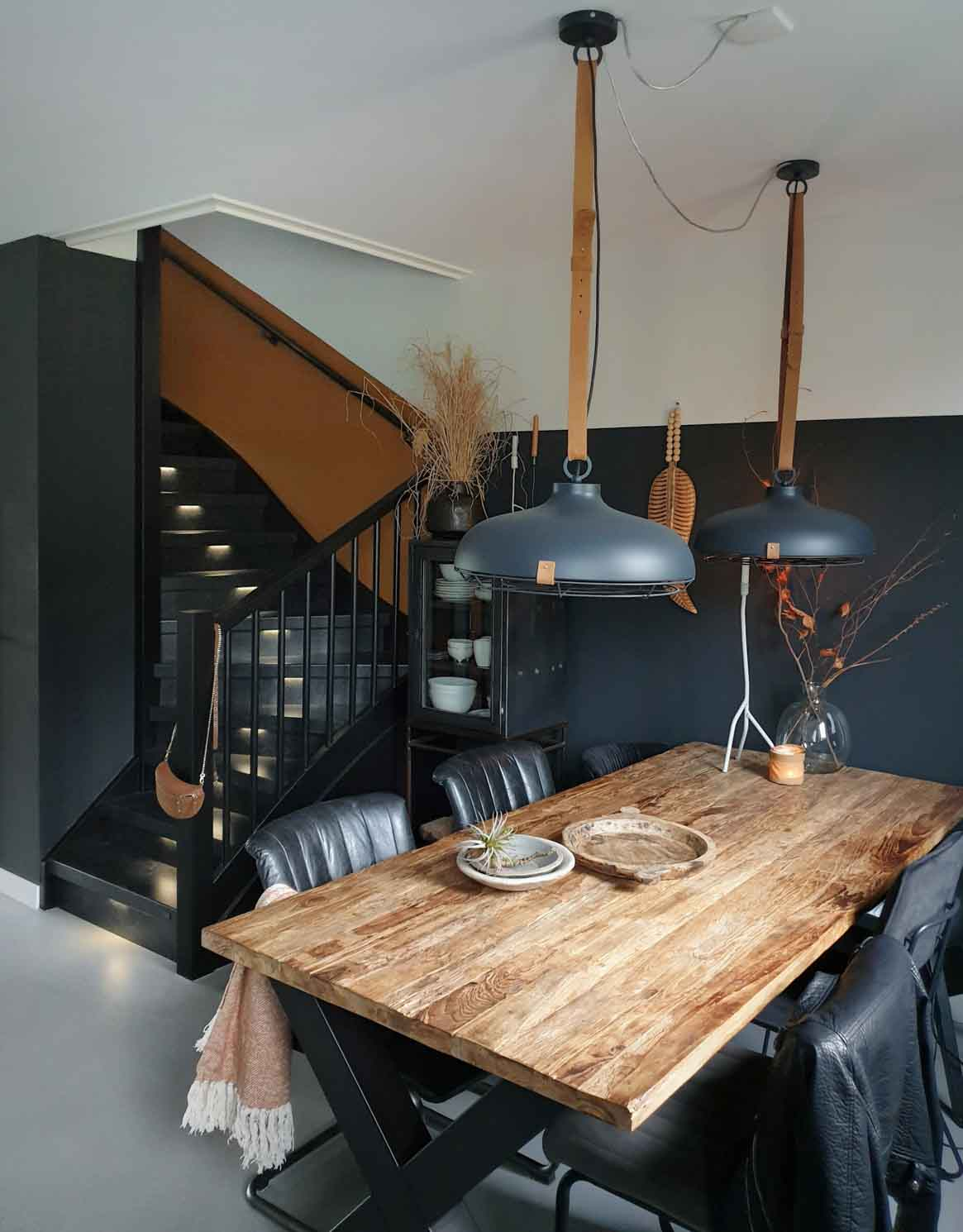 An industrial interior at Judith Huizedop´s home, wood and metal table, black leather chairs