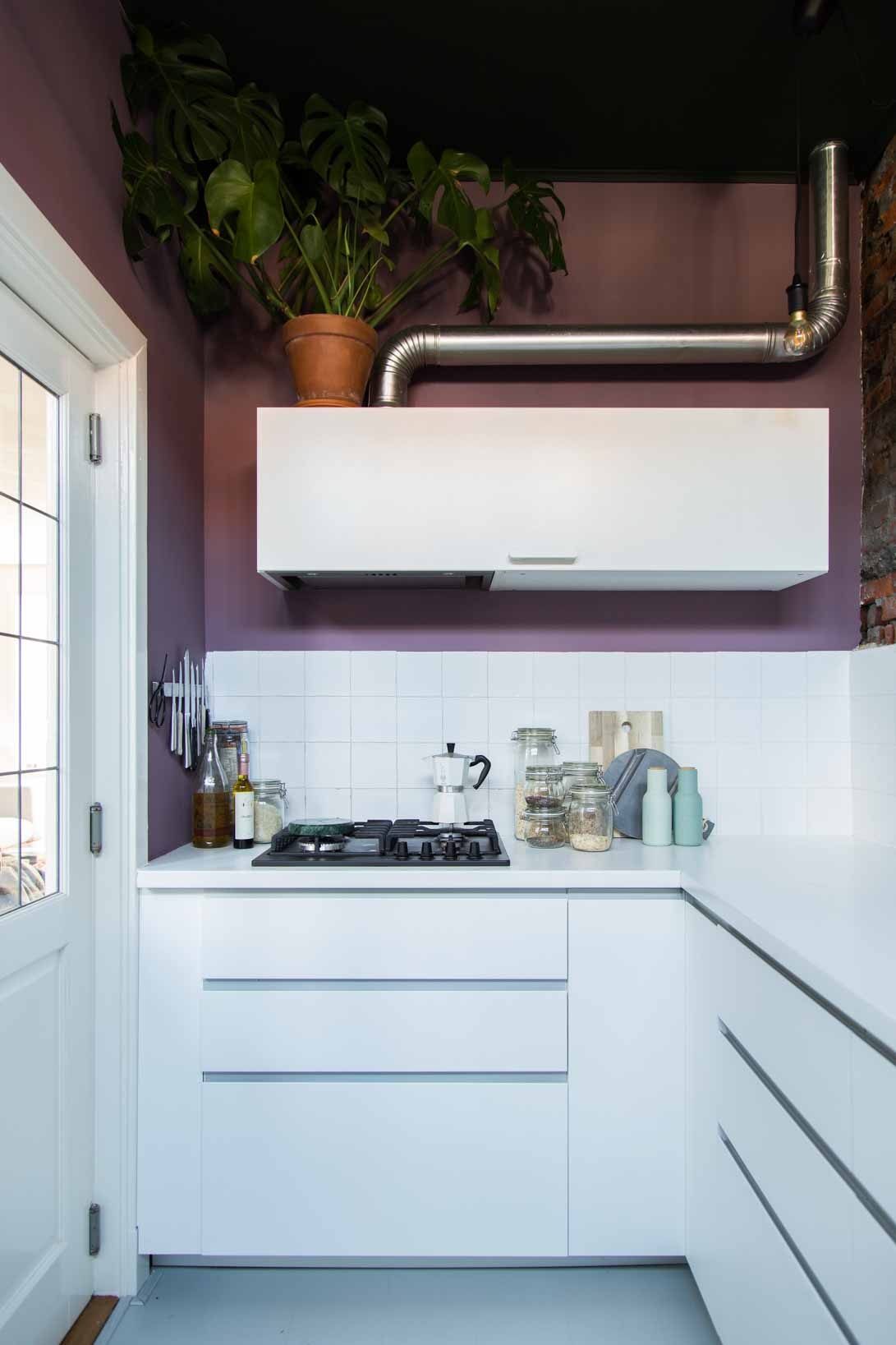 A white kitchen with purple Classico walls and a dark green ceiling
