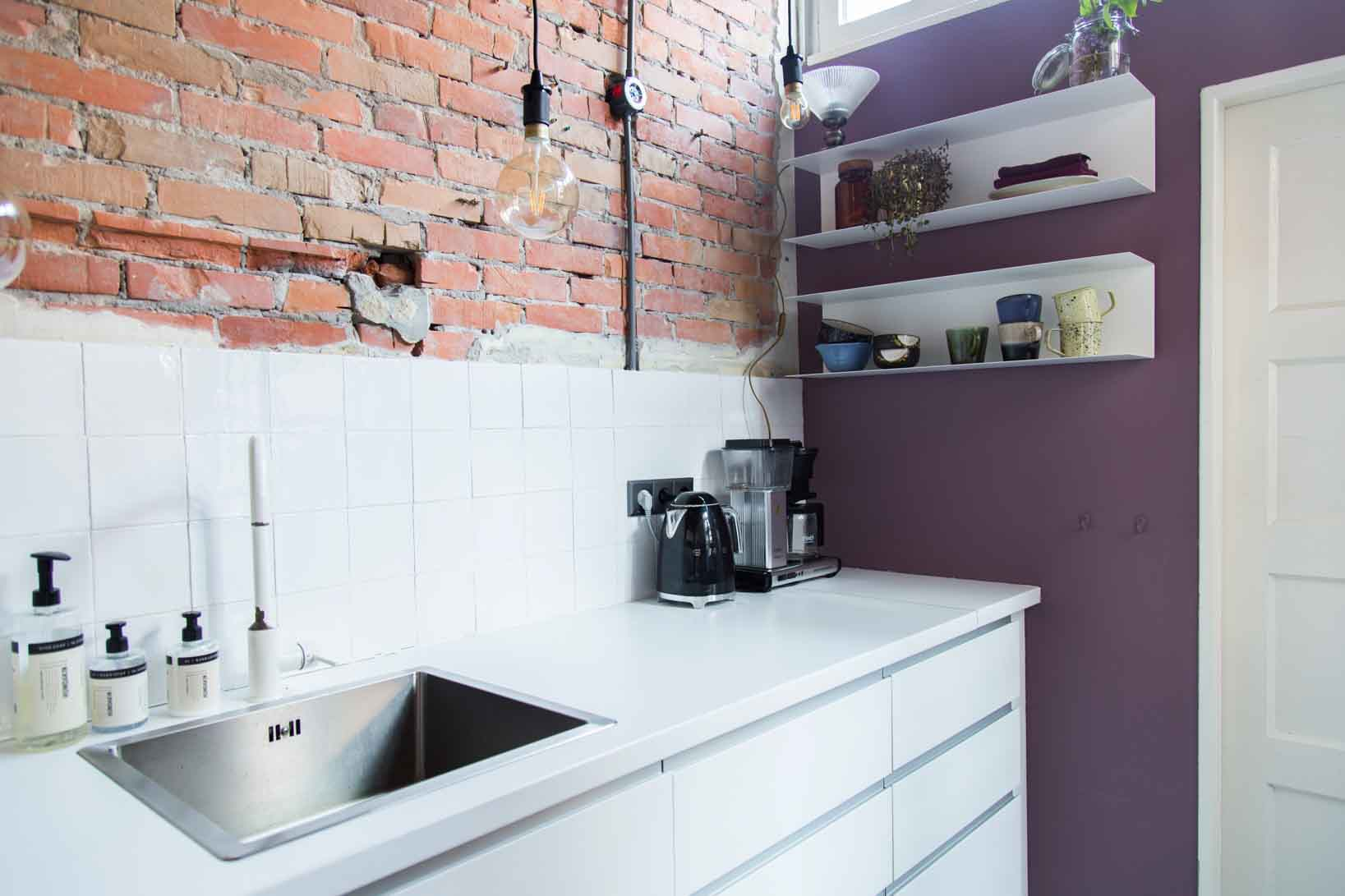 Red bricks, purple kitchen paint walls and a fresh white kitchen with black accents