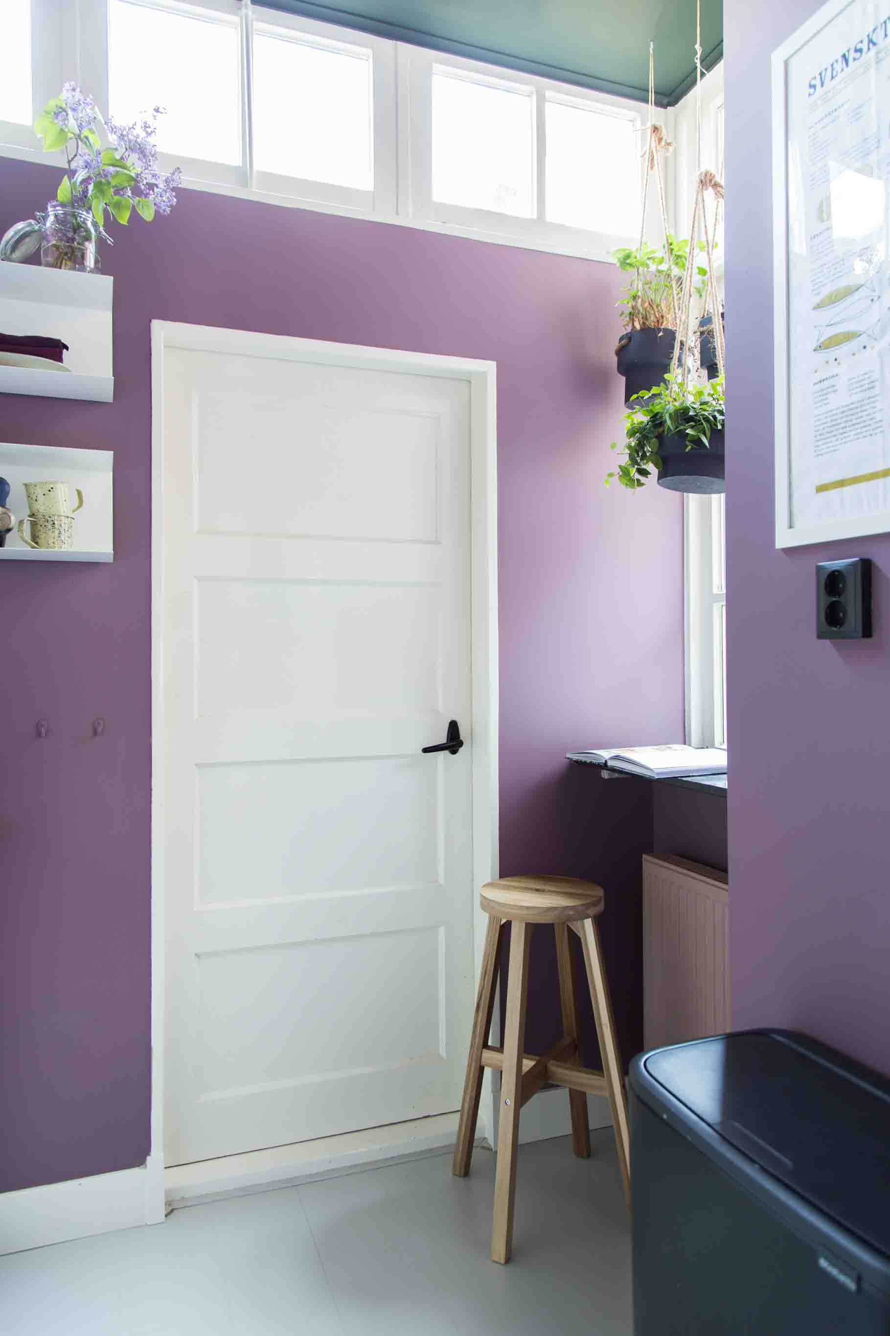 Combination of pinkish purple walls with a dark green ceiling and white doors