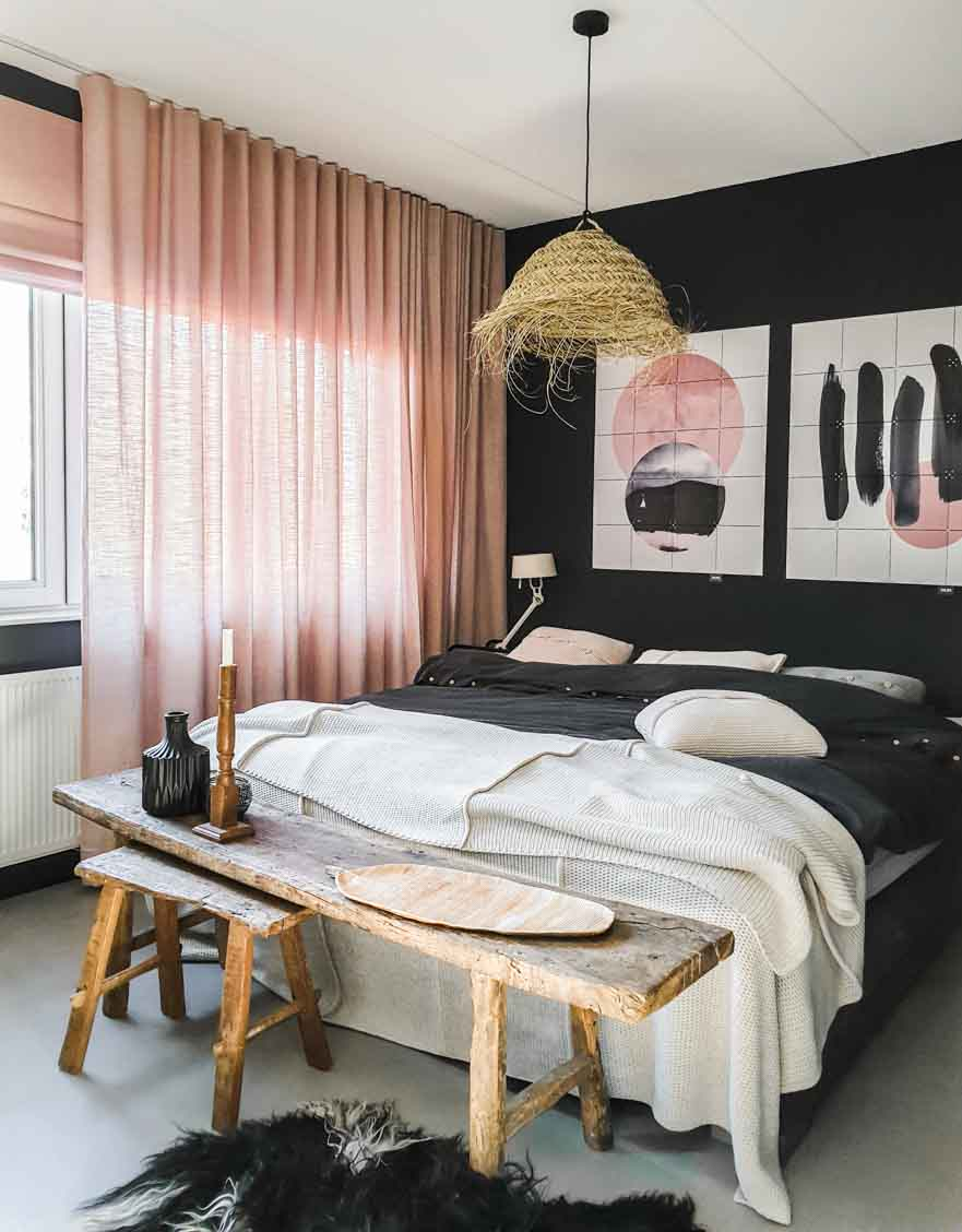 Bedroom with sheepskin rug, wooden benches at foot of the bed, soft pink curtains, and two pieces of