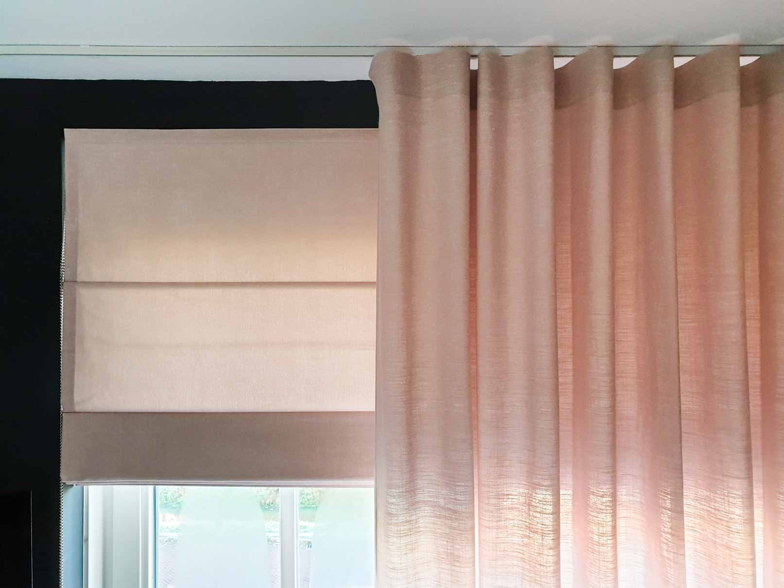 Light pink roman blinds and outer curtain in the colour Skin Powder with a black wall surrounding th