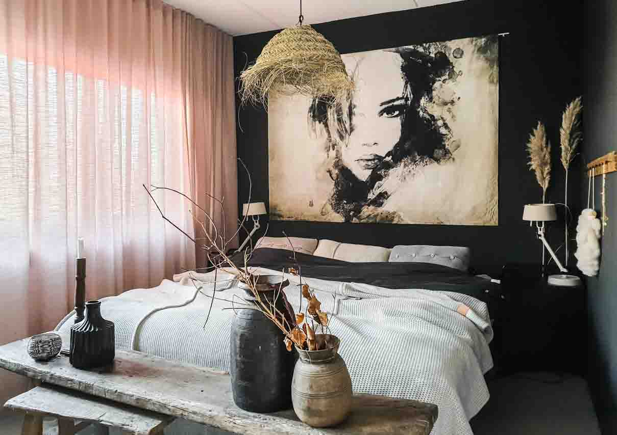 Bedroom with large bed, soft pink linen look curtains, black walls, large art with female portrait o