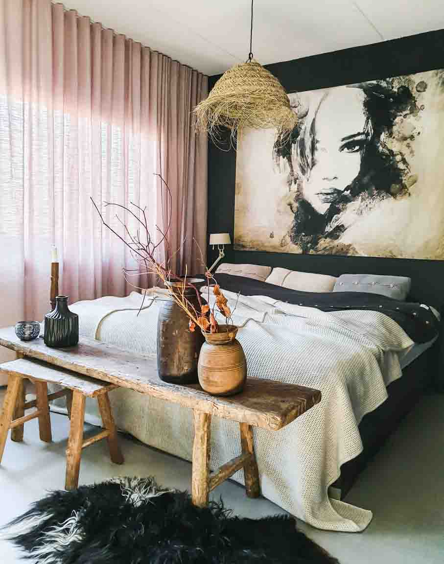 Bedroom with sheepskin rug, wooden benches at foot of the bed and twig decoration in vase, soft pink