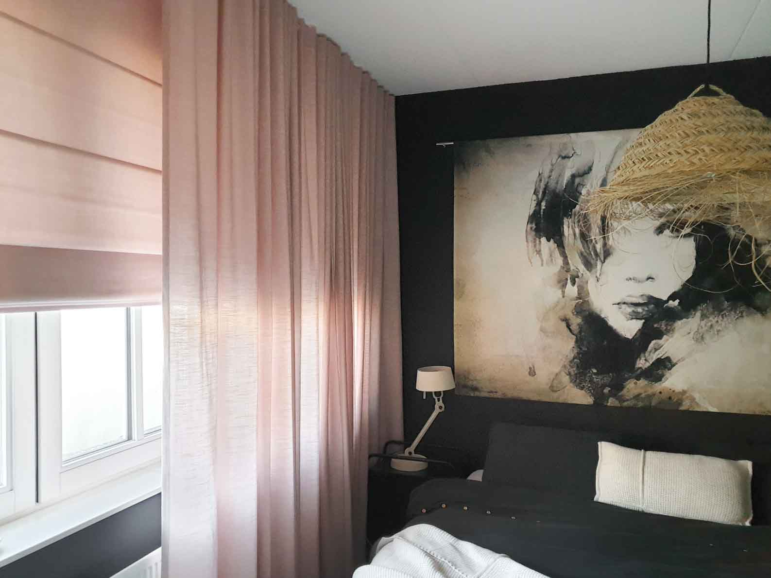 Bedroom with soft pink linen look curtains, black walls, large art with female portrait on back wall