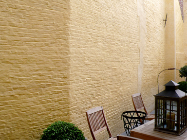 Pastel yellow painted brick wall with wooden garden furniture