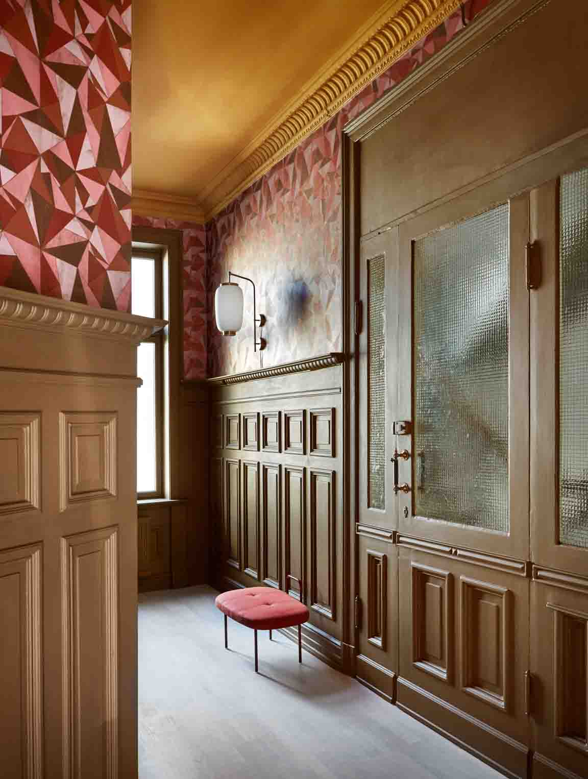 Hallway with light brown walls, red motif wallpaper, and ochre yellow ceiling