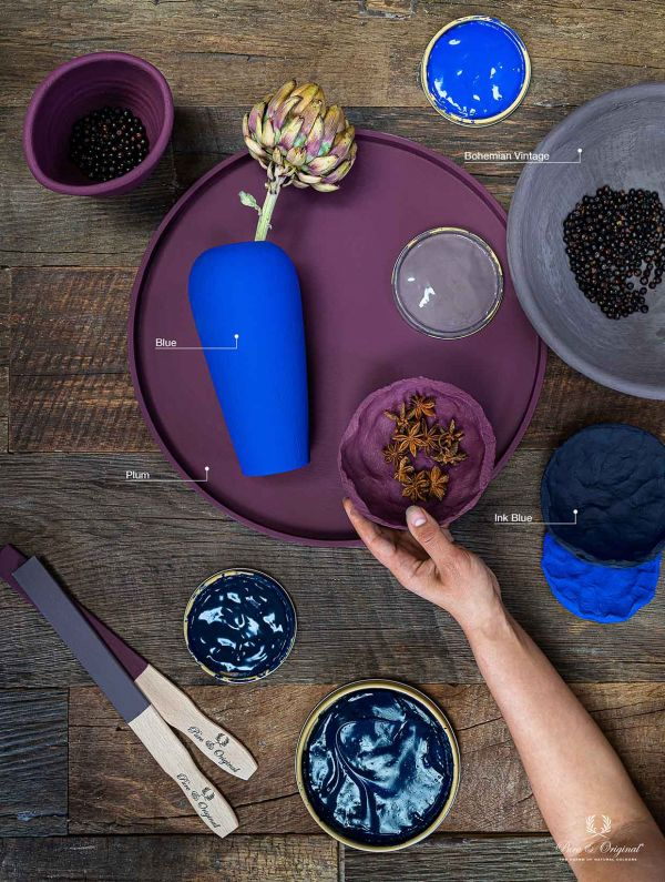 Purple, blue and grey autumn winter inspiration. Purple tray, blue vase, paint can, hand holding bow