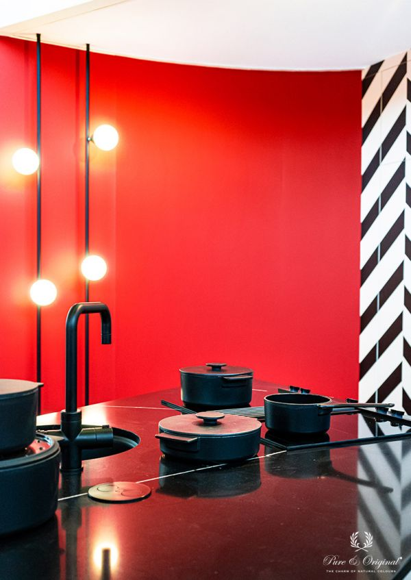 Kitchen in red and black with geometric wallpaper, black crane and black kitchen counter
