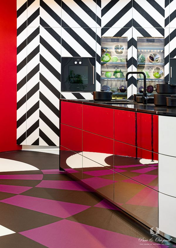 Kitchen in red, black and white. Mirror kitchen cabinets, geometric wallpaper, black crane and pans