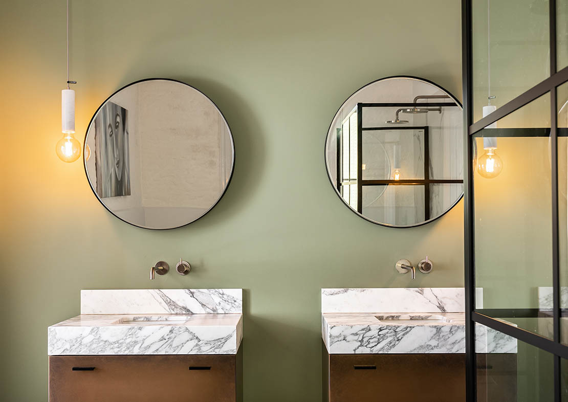 Washable wallpaint in this green bathroom with trendy round mirrors