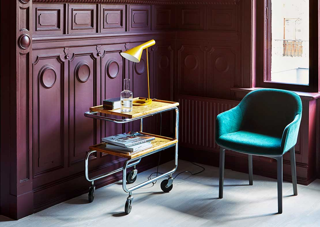 Historical property with modern design interior, green velvet chair, wooden trolly and yellow desklamp