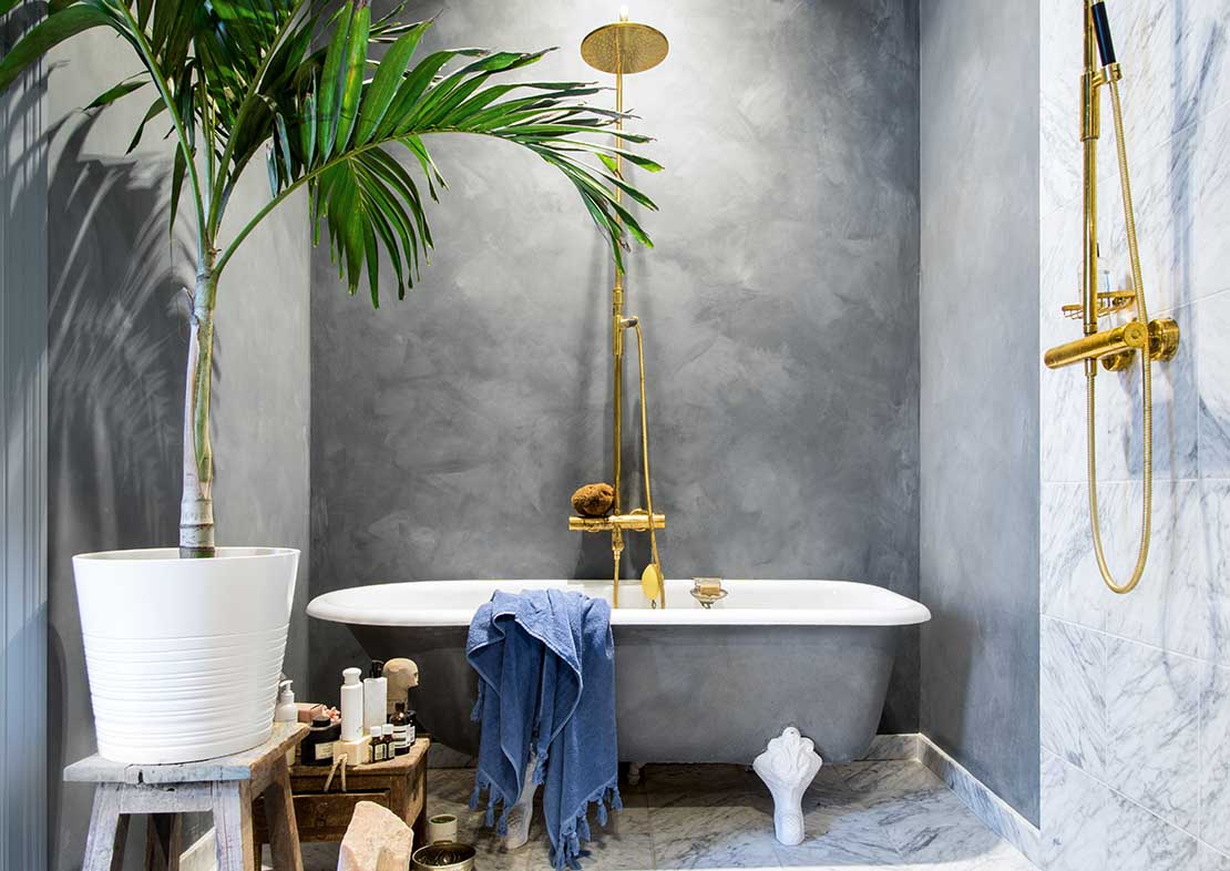 Bathroom with lime paint in grey blue colour. Gold shower, classic bath and palm plant