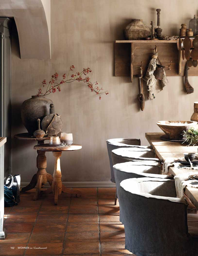 Dining room with a long rectangle table, grey brown walls, and rust coloured floor tiles