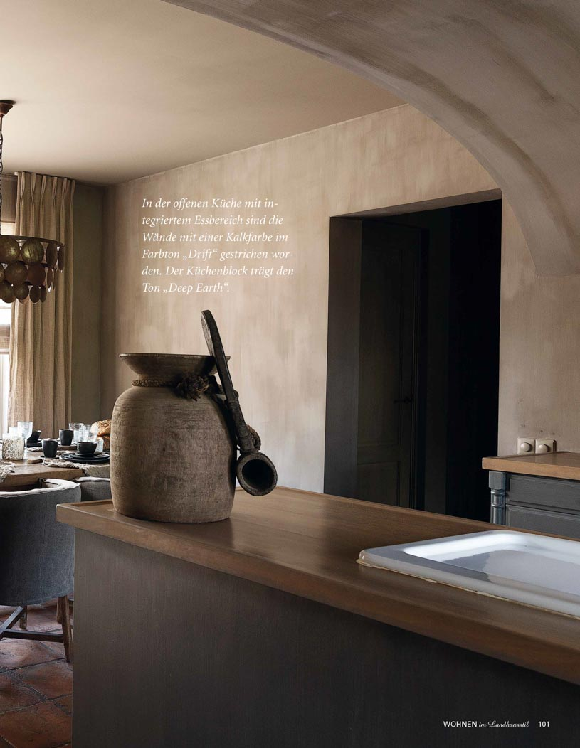 Kitchen and dining area with grey brown walls and ceiling, wooden countertop and an antique pot with
